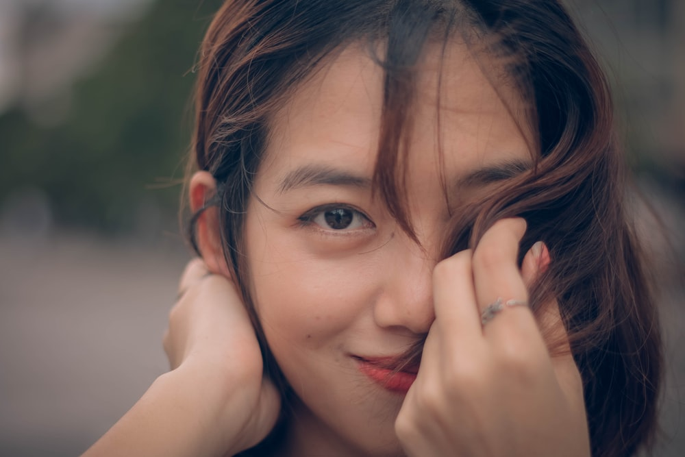 selective focus photography of woman covering her face