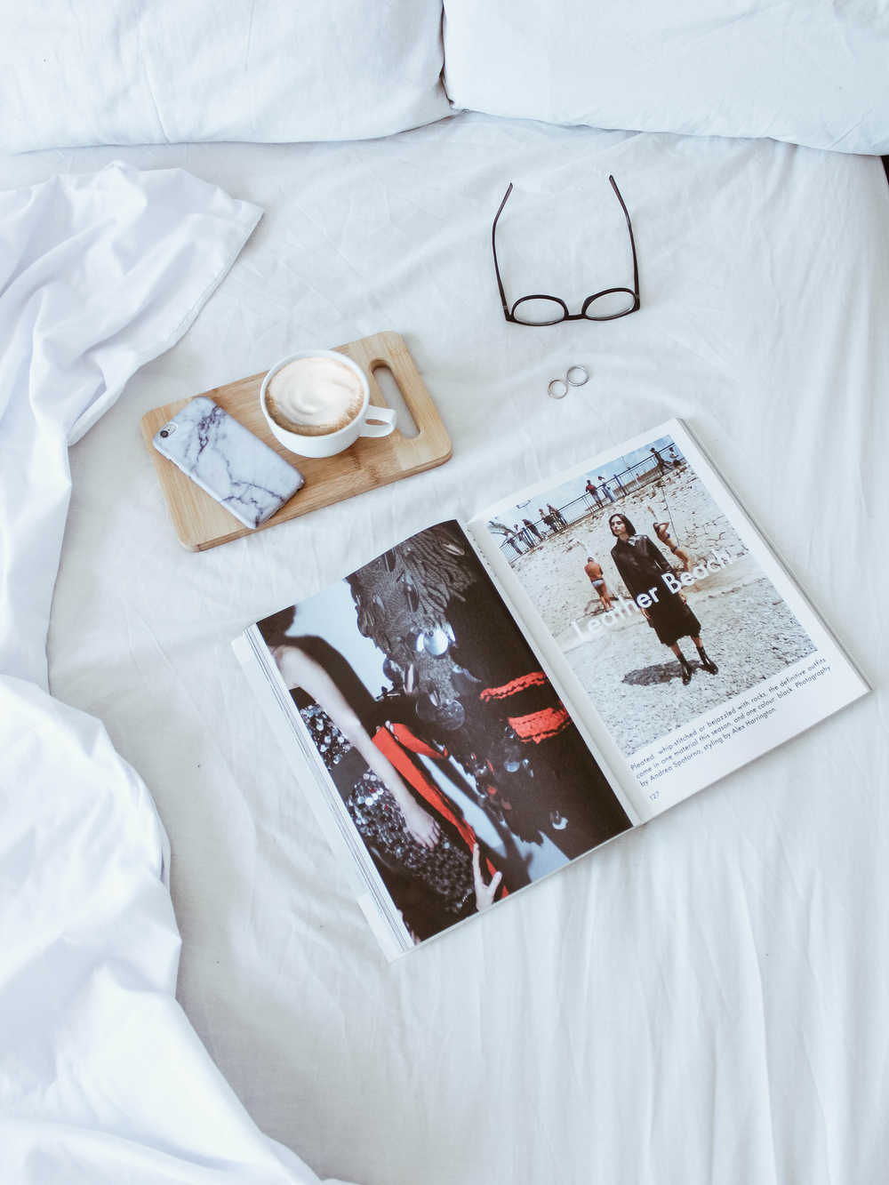 leather beach magazine on top of white comforter