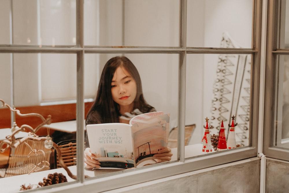 woman reading a book near window