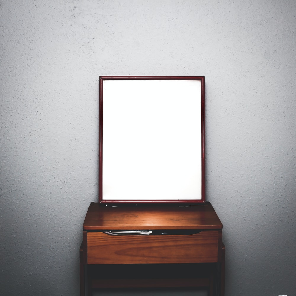 brown wooden dresser with mirror inside white room
