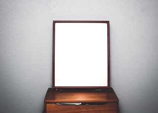 brown wooden dresser with mirror inside white room