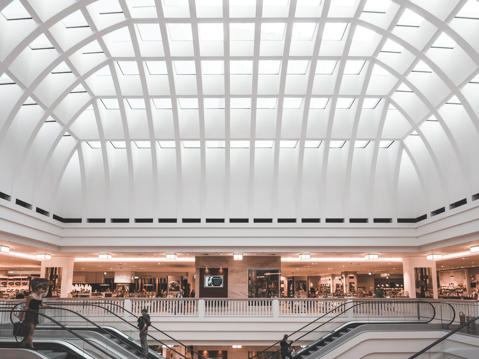 A shopping mall with a large white domed ceiling