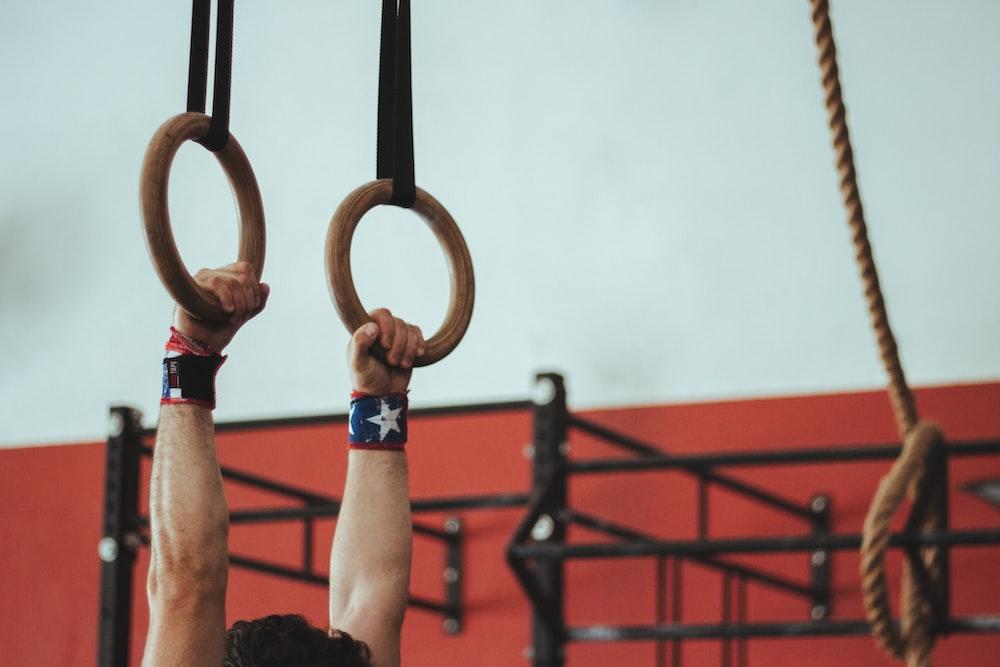 man hanged on brown rings
