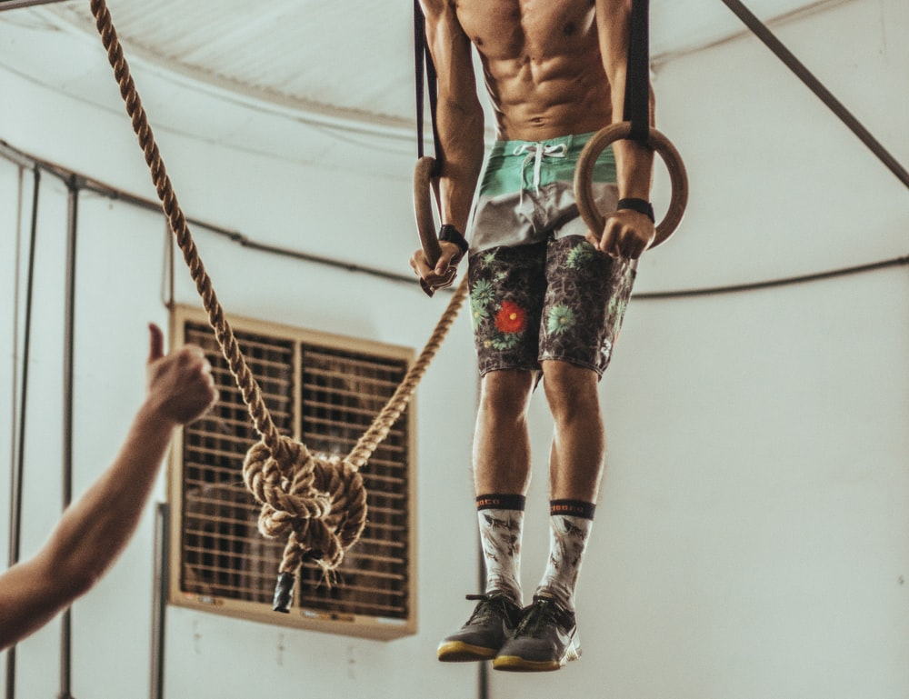 man wearing multicolored shorts while exercising on rope inside white room