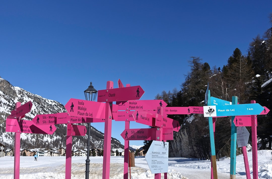 Winter. Road signs over iced lake of Sankt Moritz. Wherever you want to go, be sure to put your feet inside a pair of Timberland.