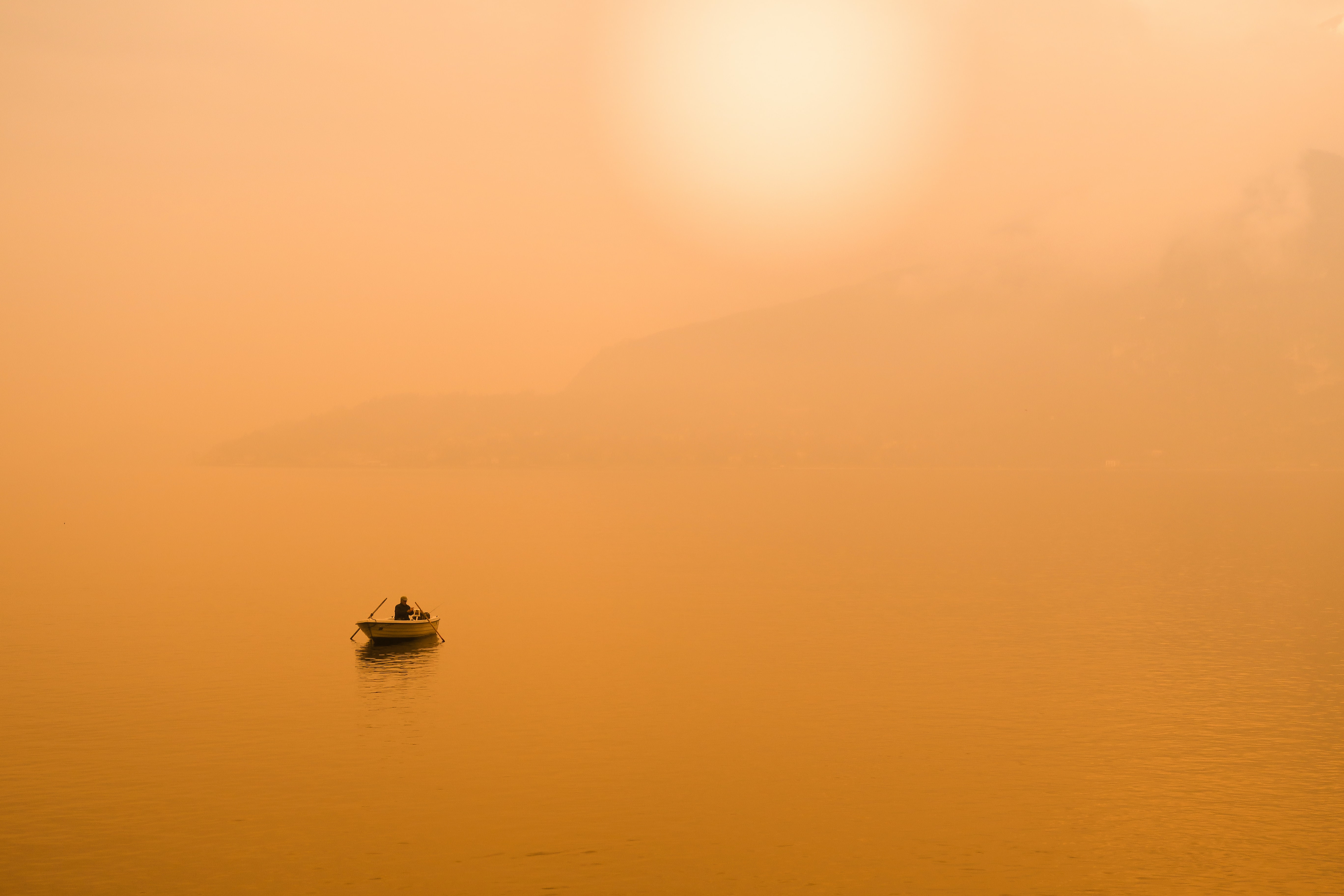silhouette photography of person in gray sailing boat in the middle of body of water