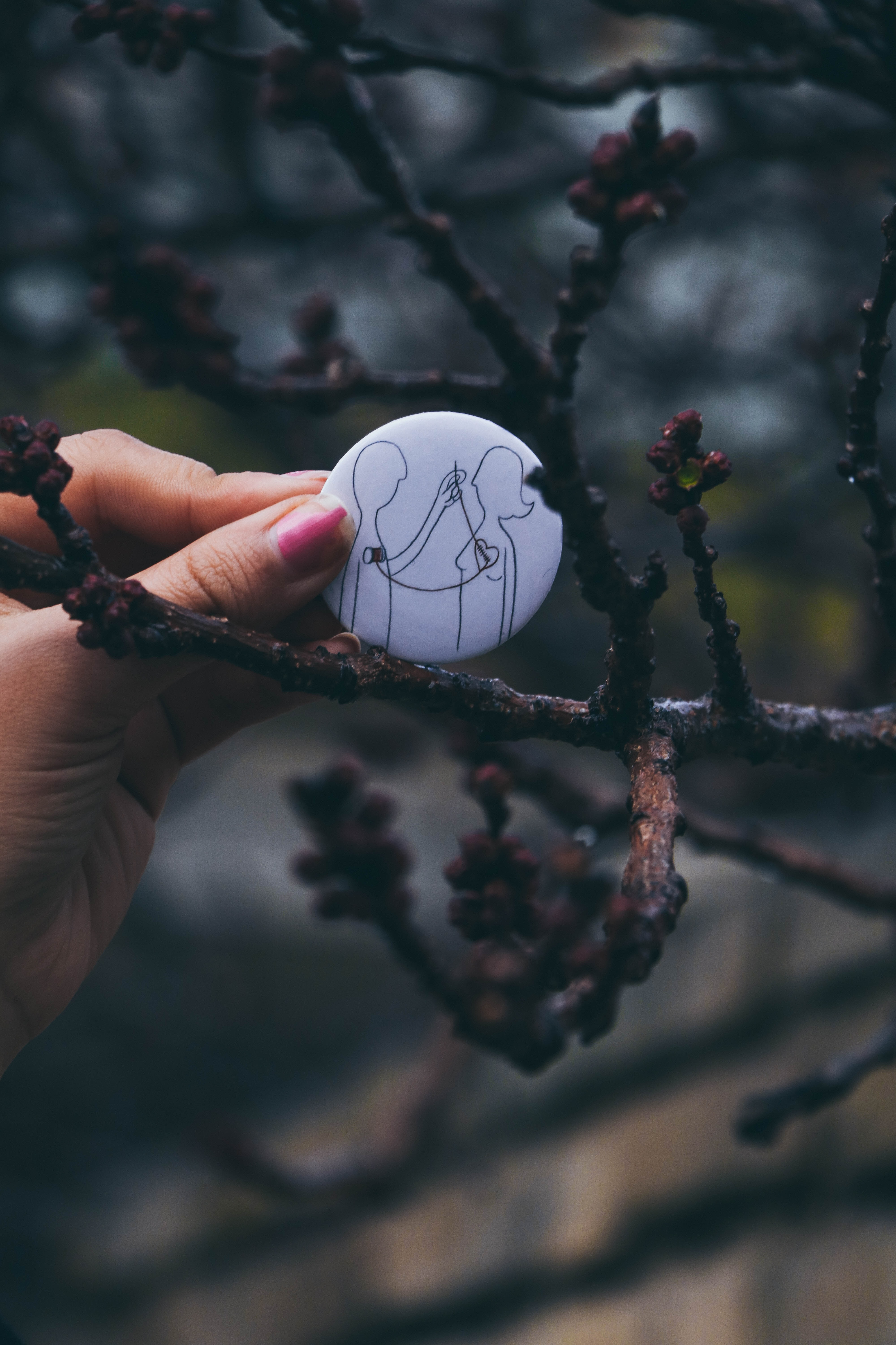 selective focus photo of person holding white pinback button
