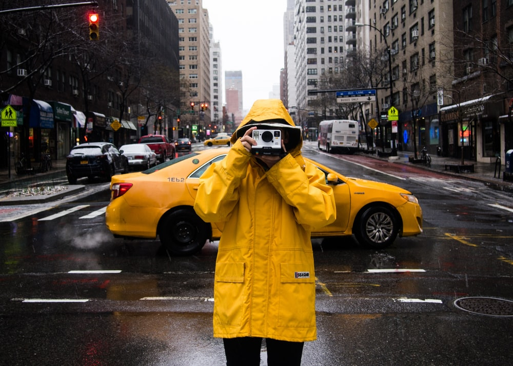 man standing on road while holding camera