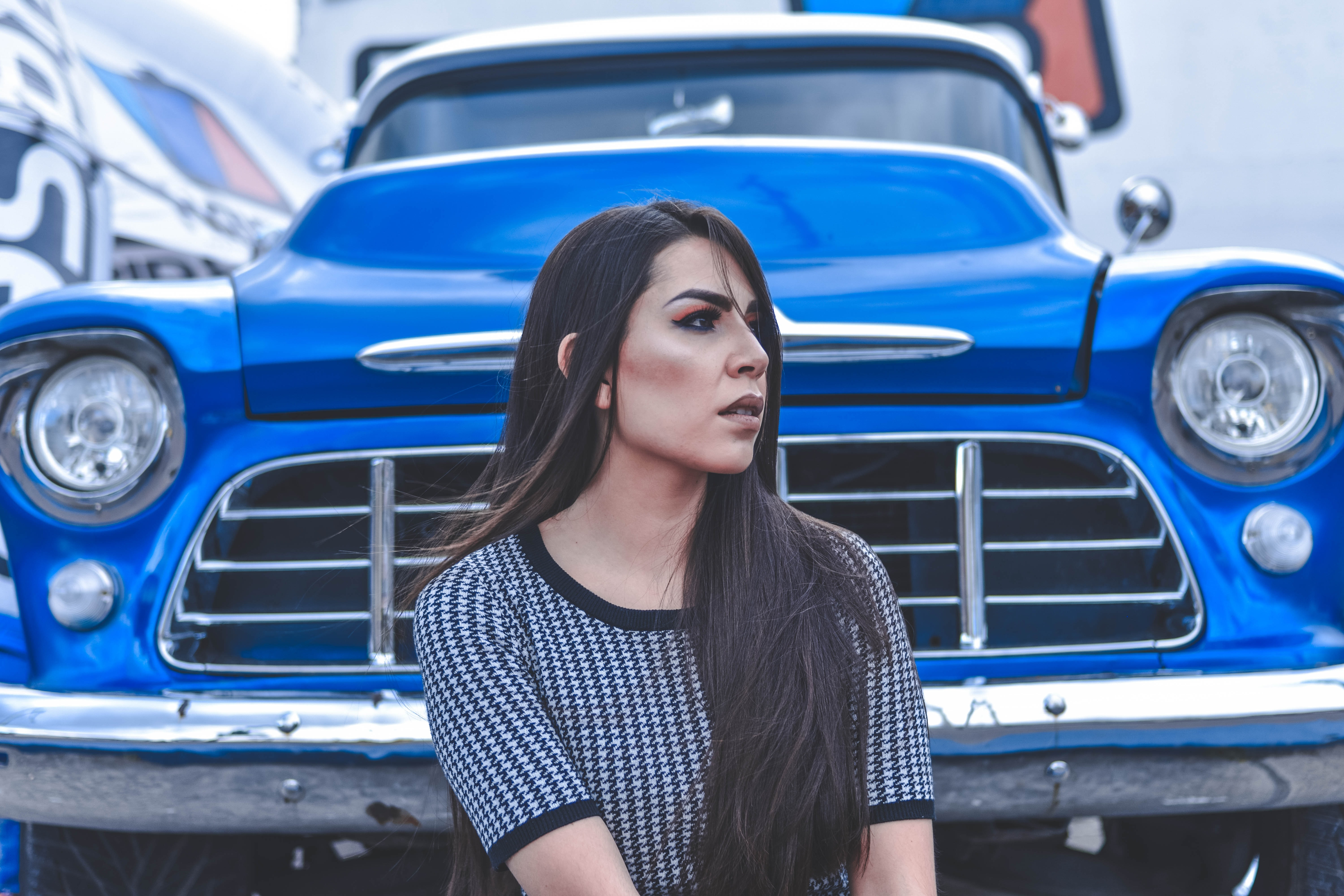 woman sitting beside blue car