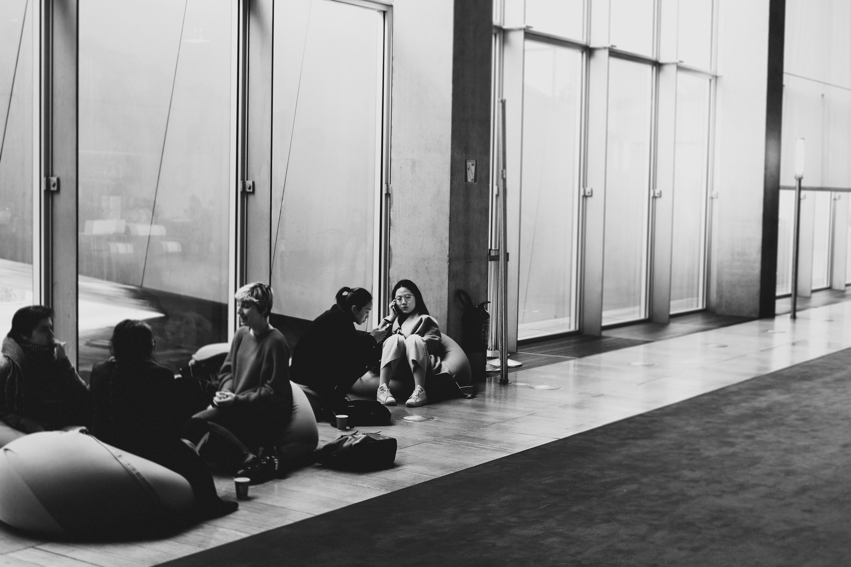 greyscale photography of people sitting on floor