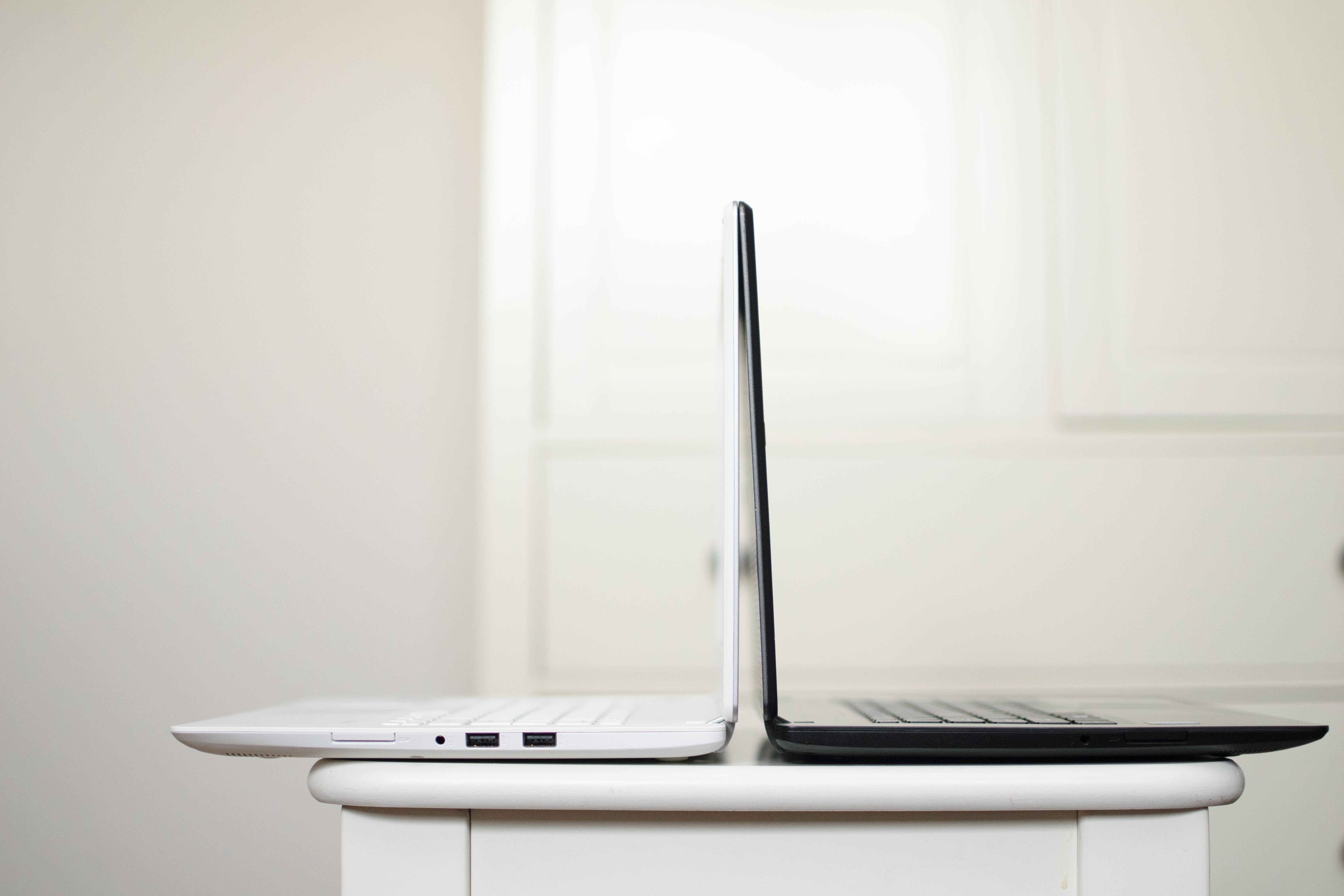 black and white laptop on table back to back