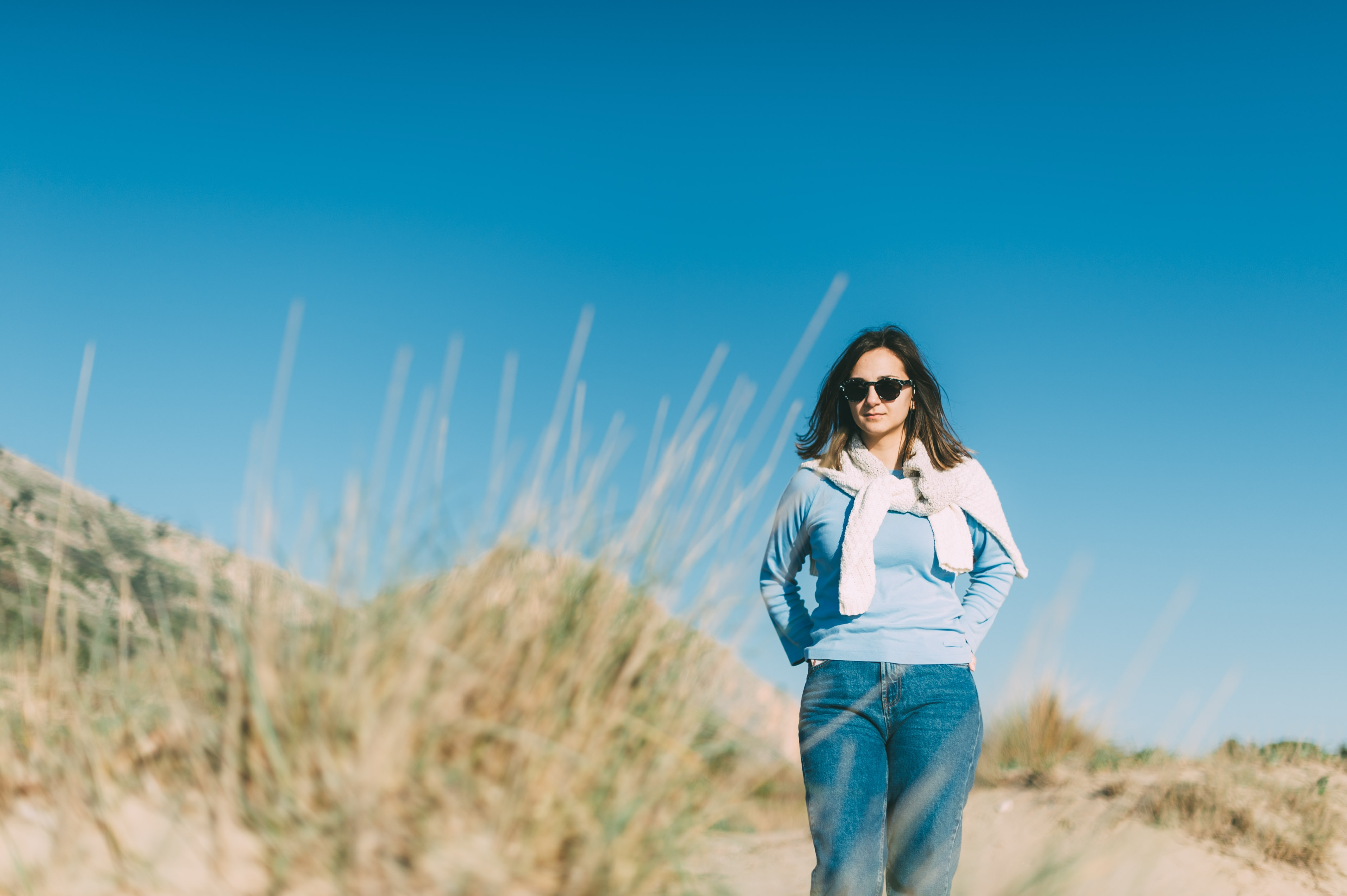 woman wearing blue sweater and blue jeans standing near grass