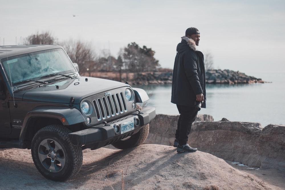 man in black parka jacket near black Jeep wrangler