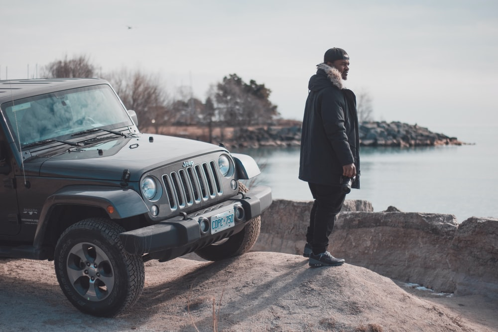man in black parka jacket near black Jeep wrangler