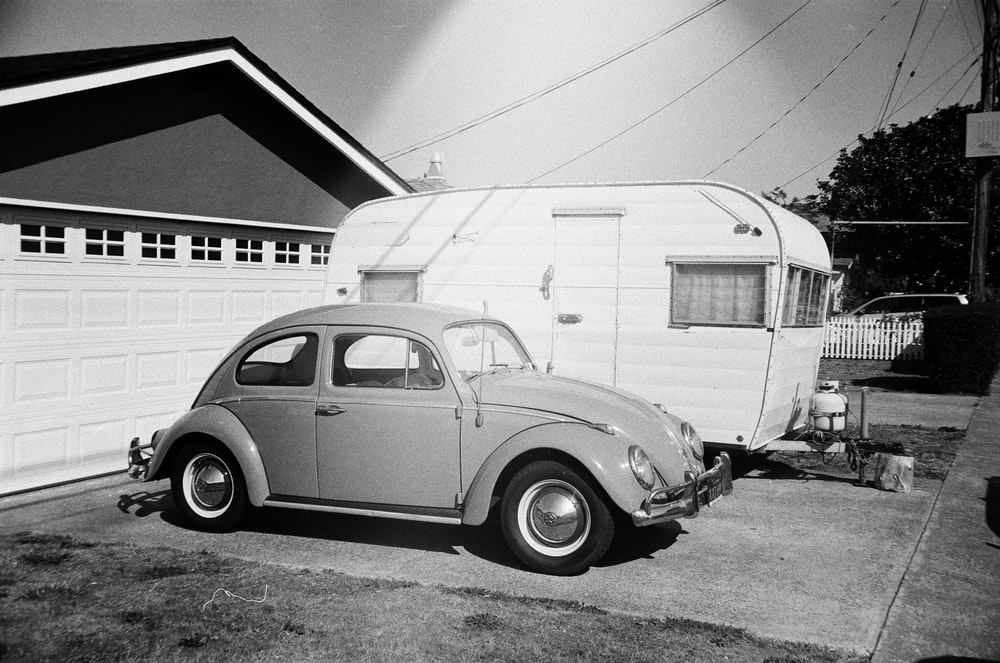 grayscale photo of Volkswagen Beetle coupe beside travel trailer parked in front of garage