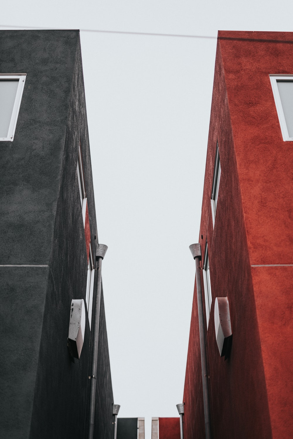 low-angle photo of two black and red concrete buildings
