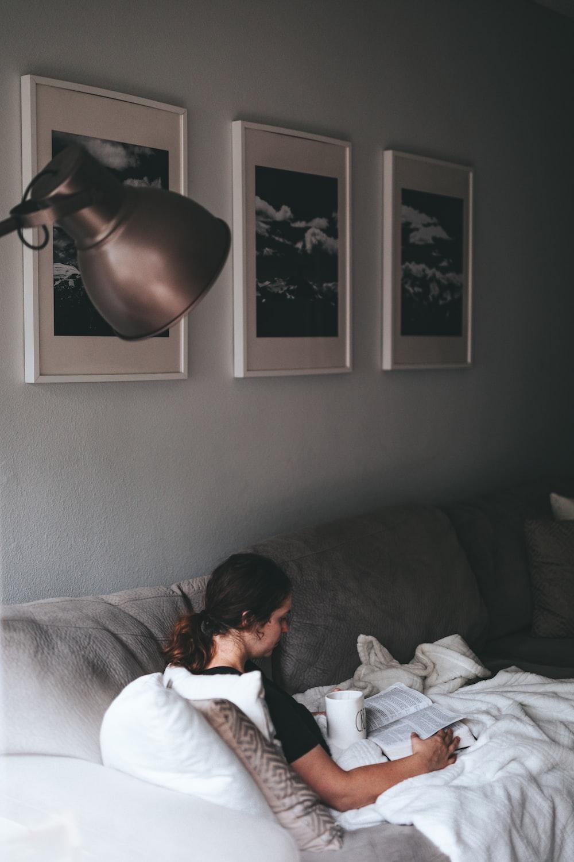 woman reading book sitting on gray sofa