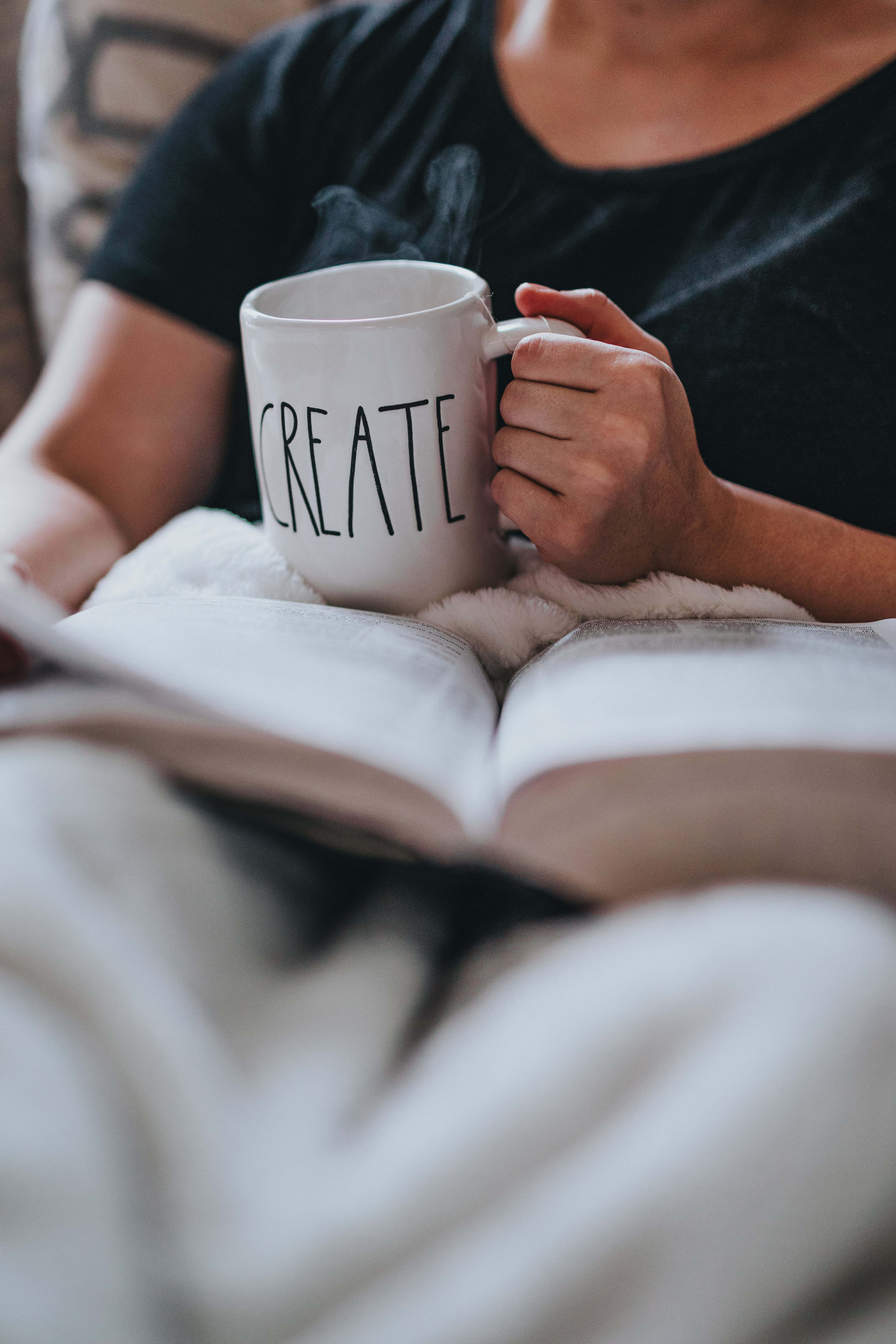 person drinking coffee while reading indoors