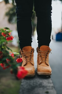person wearing pair of brown boots near flowers
