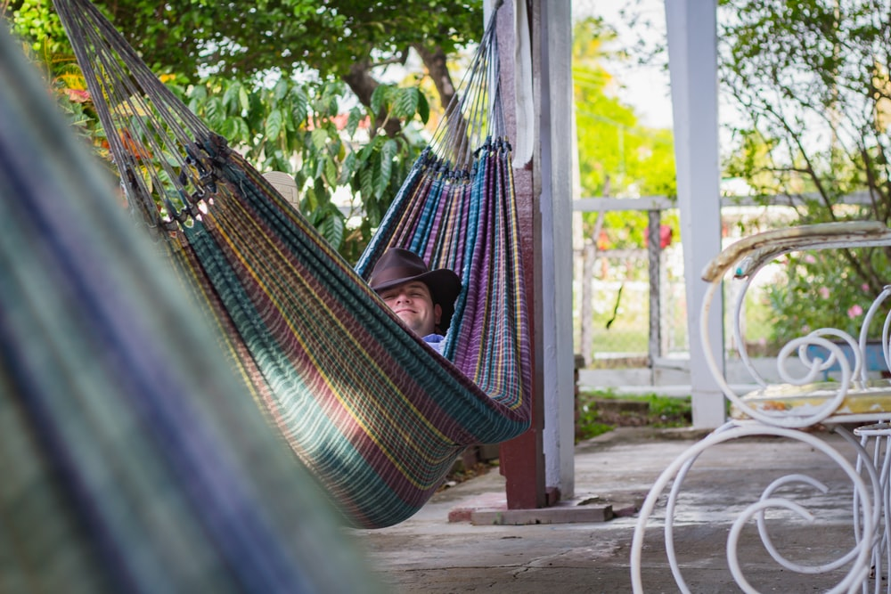 man laying down on multicolored hammock hanged on porch column