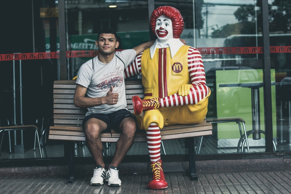 man sitting beside McDonald statue