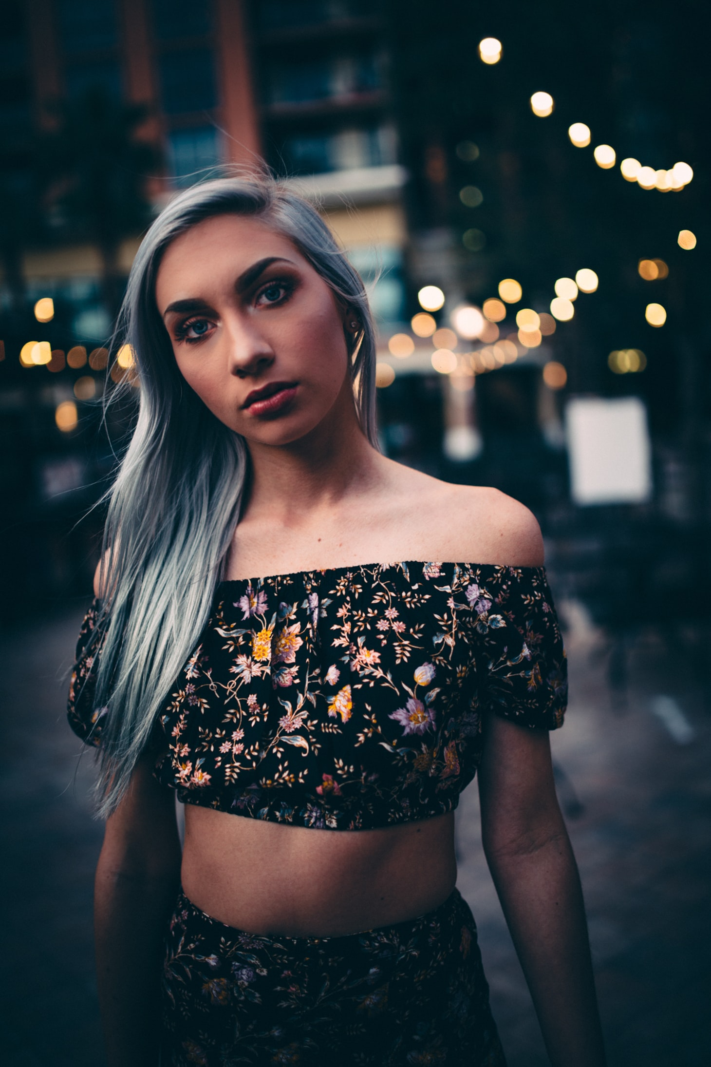 gray haired woman wearing black-and-multicolored floral 2-piece crop dress