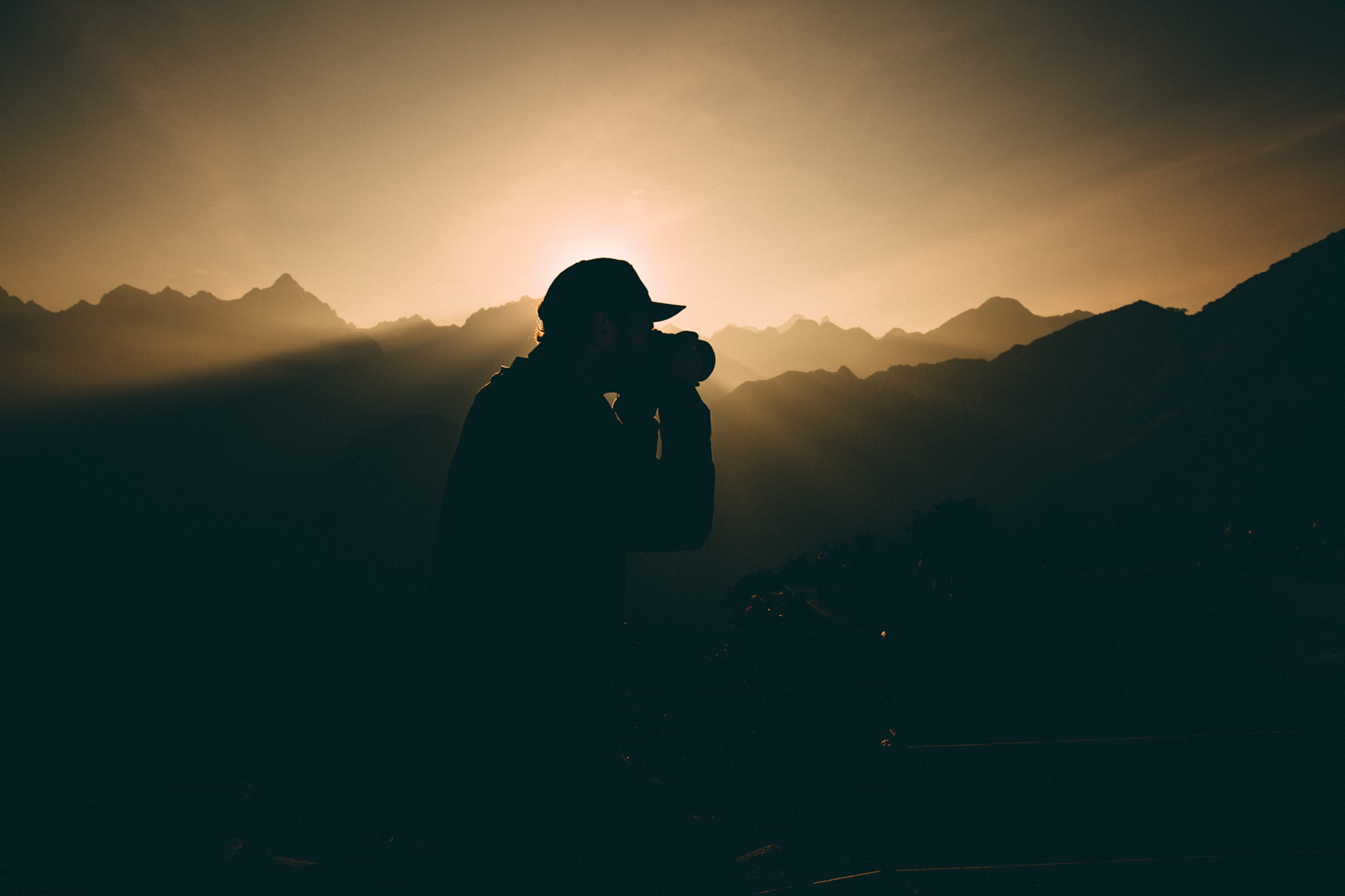 silhouette of man carrying camera near mountains during sunset