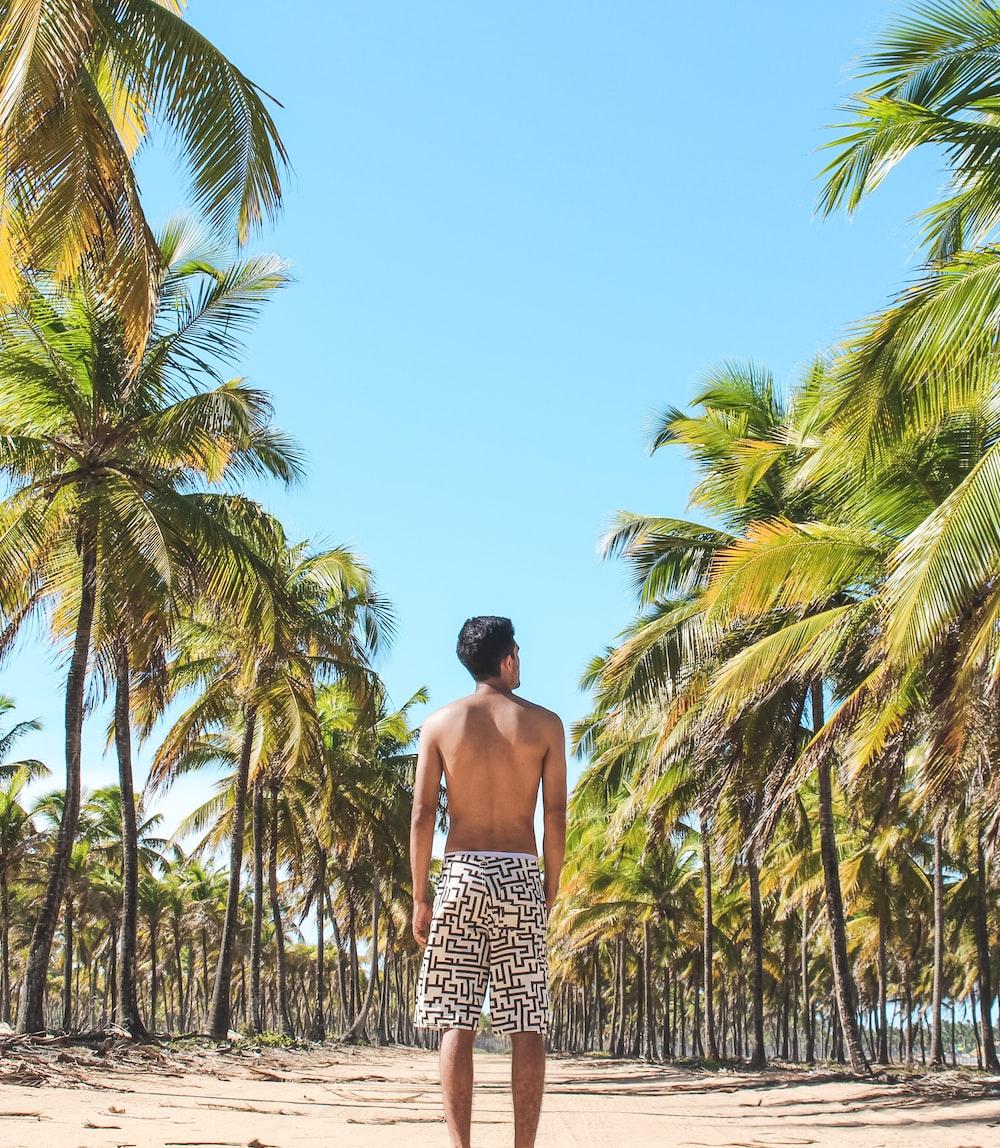 man standing on empty road in between coconut trees