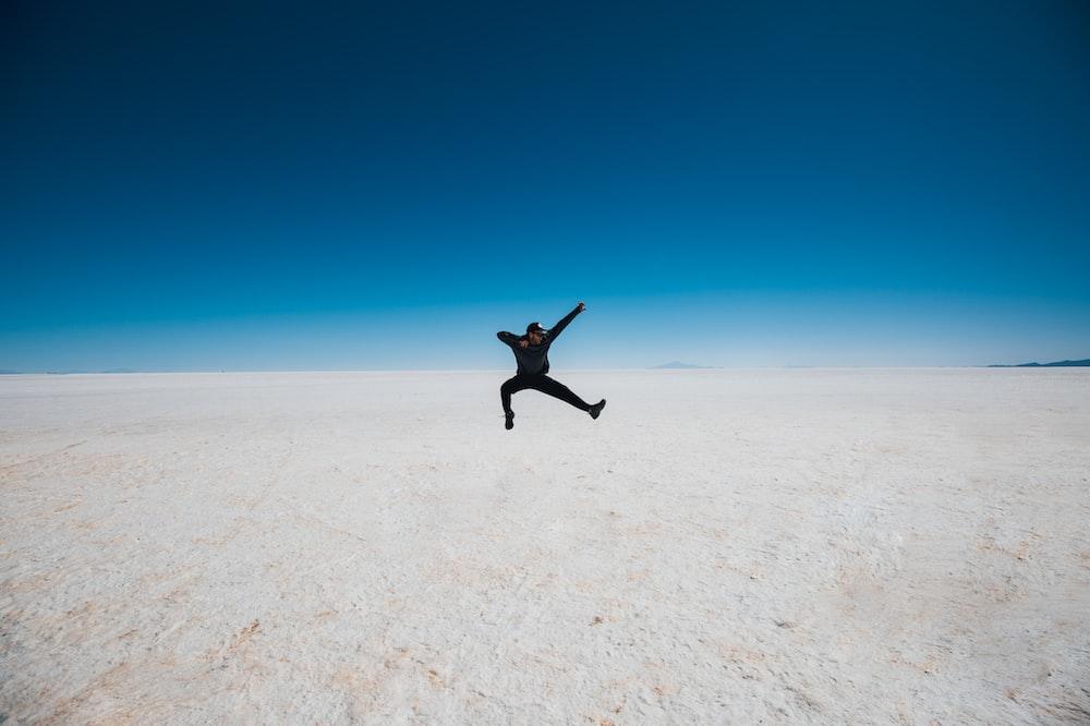 man jumping on desert