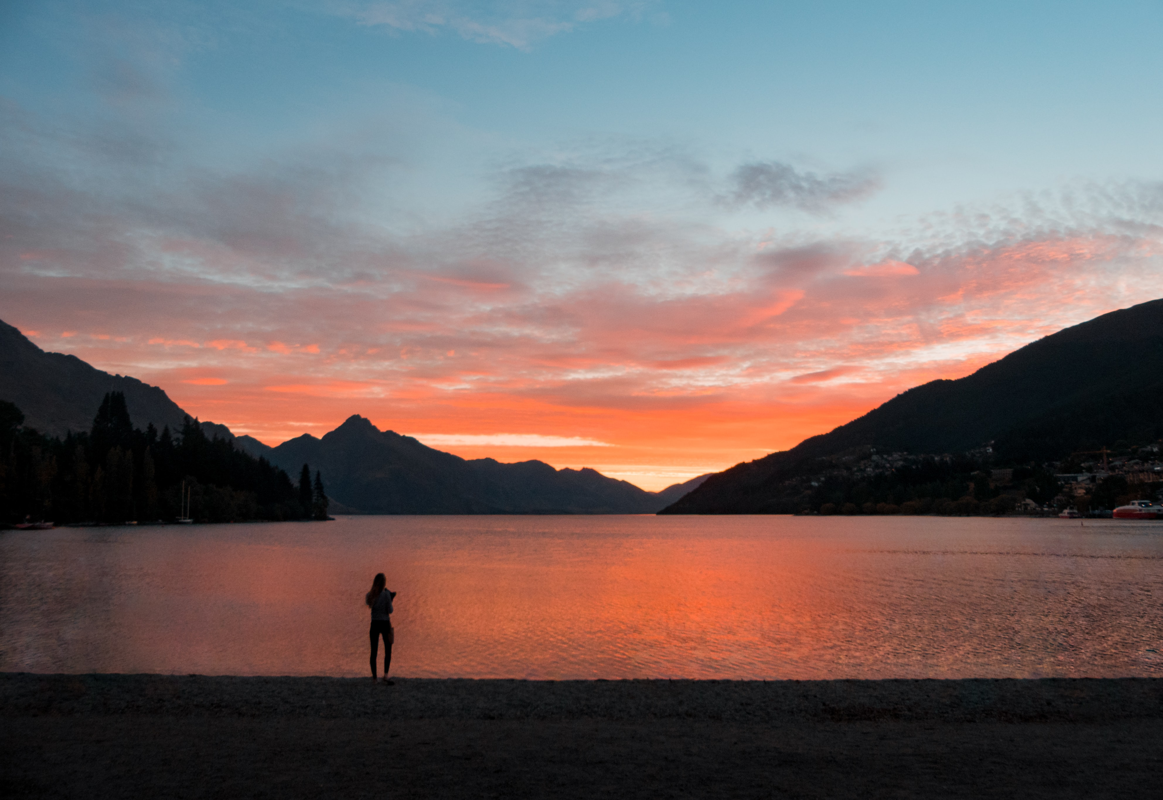 silhouette photo of woman standing while facing body of water