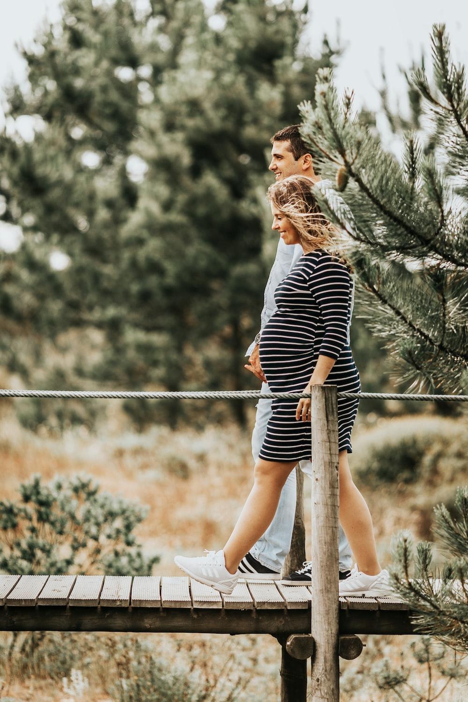 selective focus photography of couple walking on wooden bridge