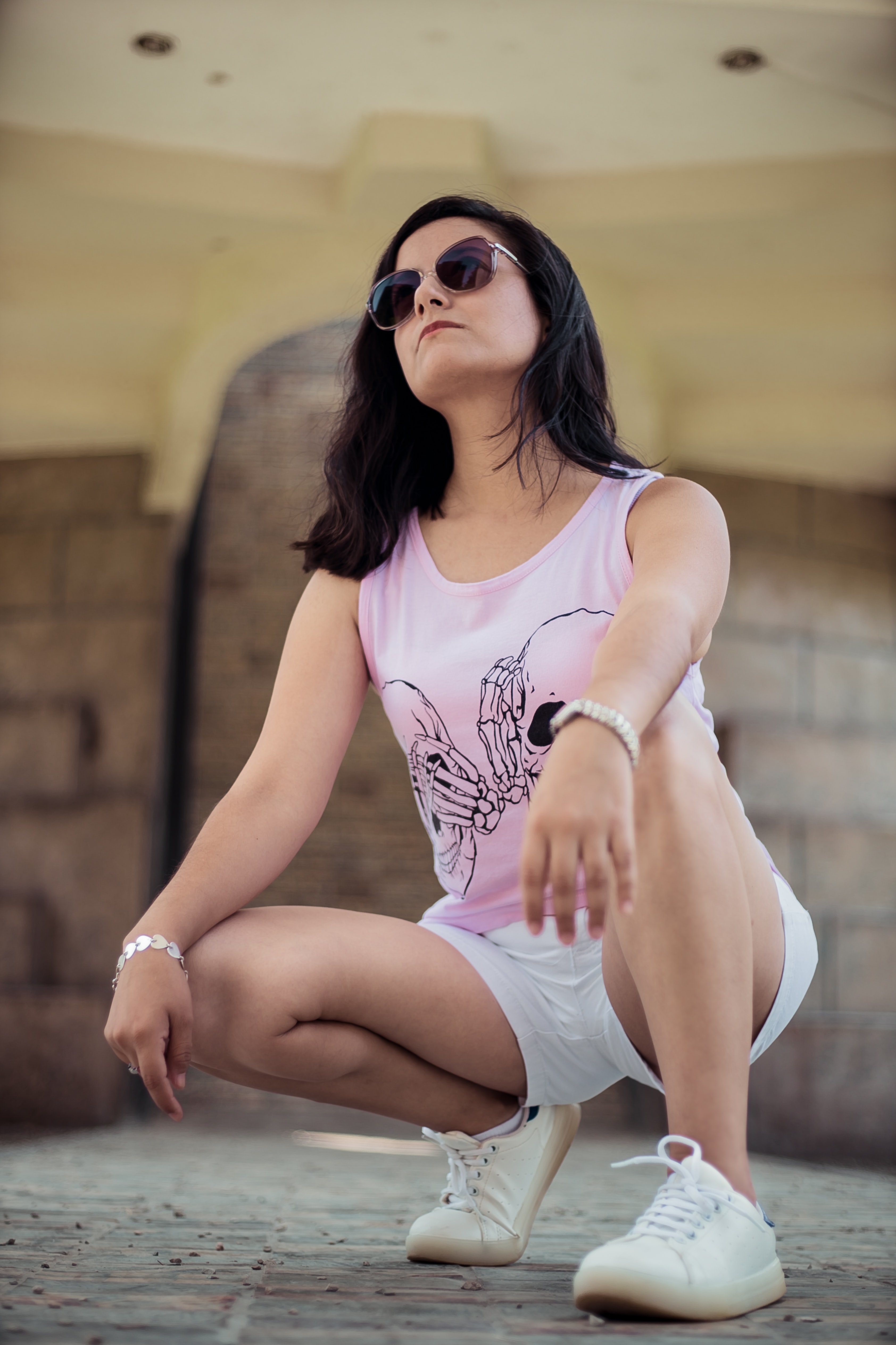 woman in pink tank and white shorts taking photo near brown concrete wall