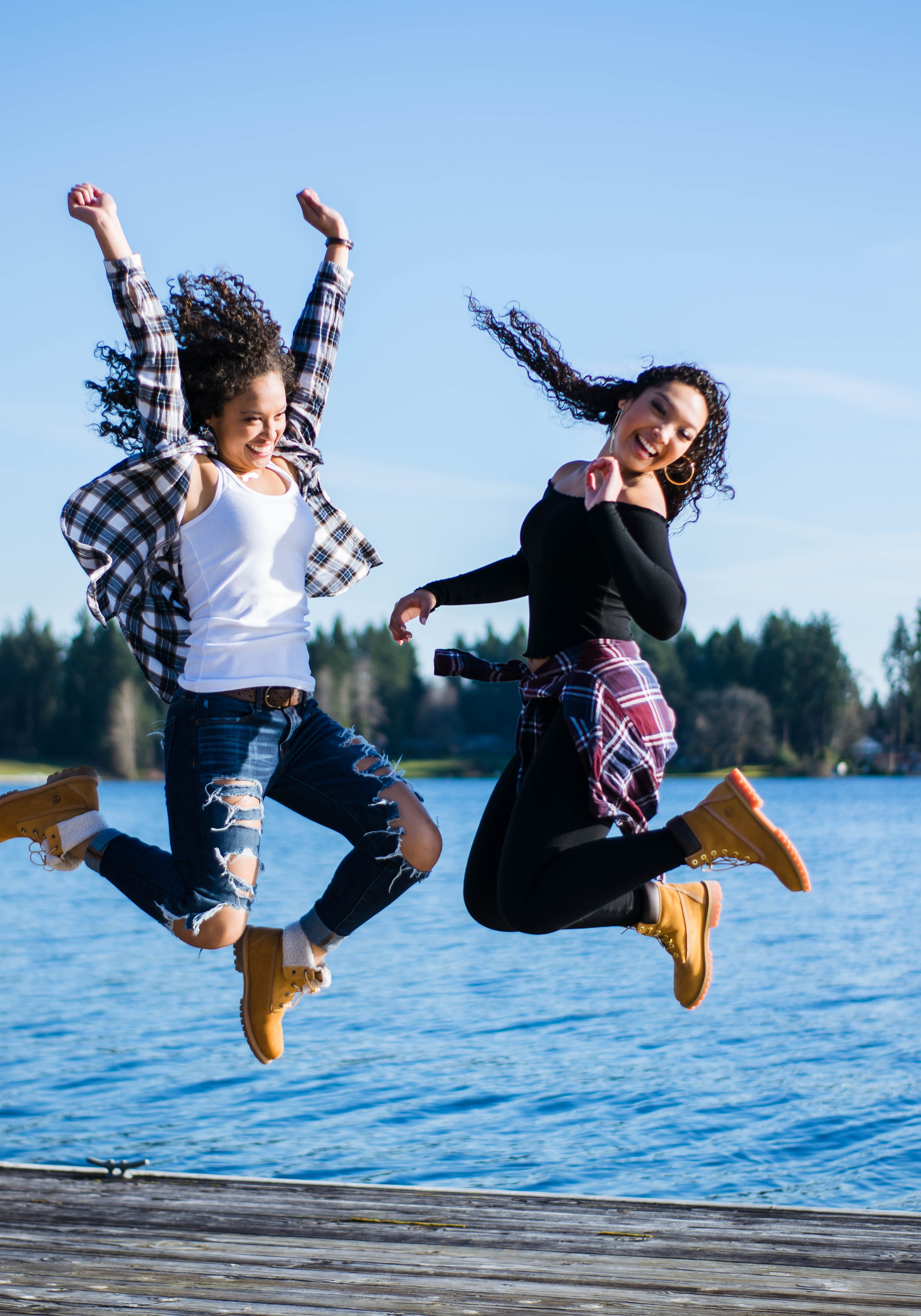 two women jumping near body of water photography