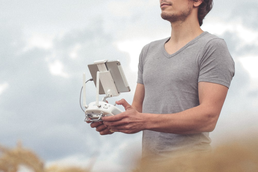 man holding white and gray drone controller