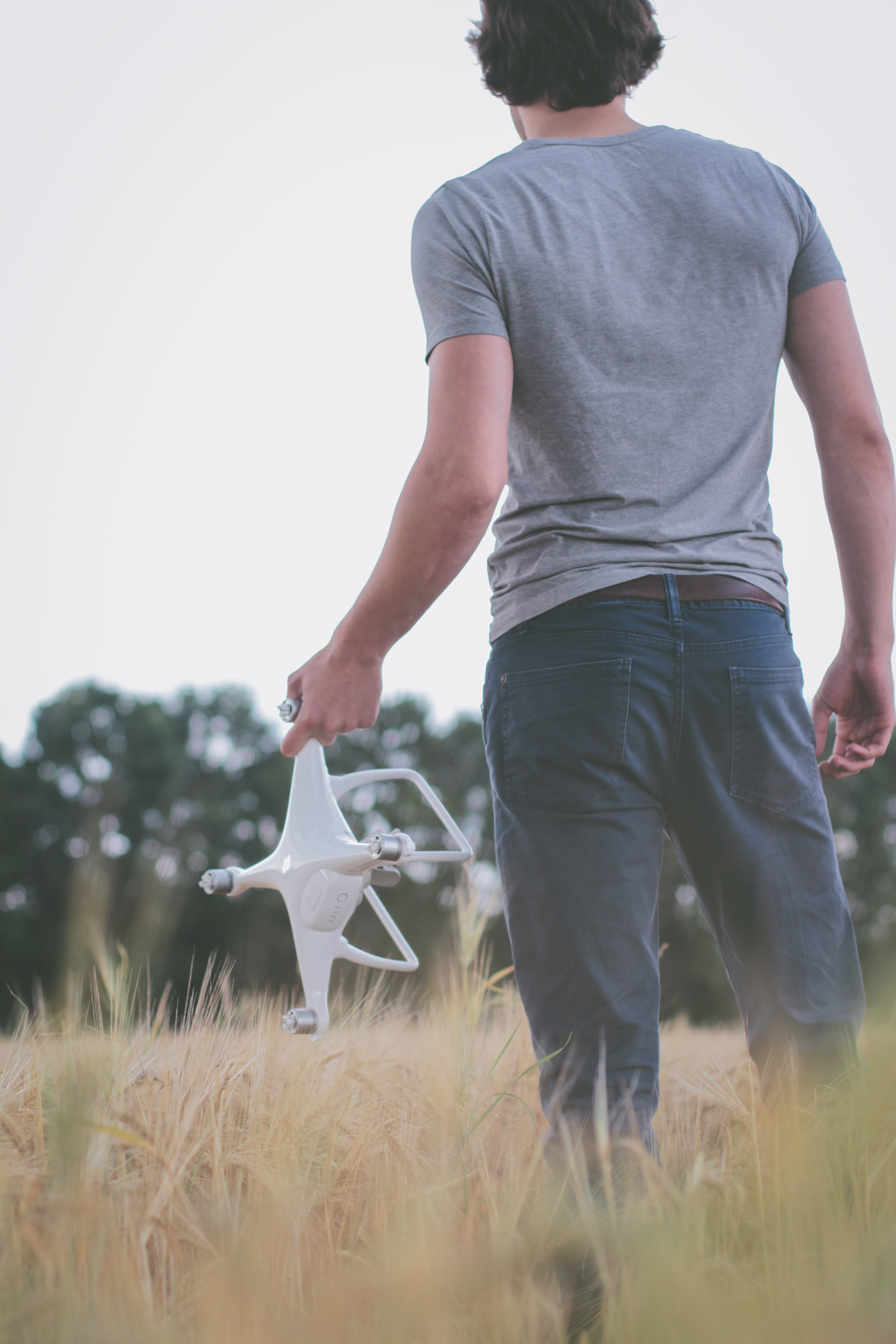 man standing on field holding white quadcopter