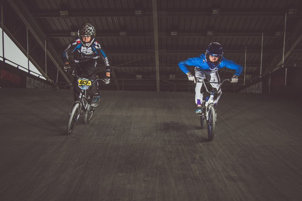 two man rides BMX bikes and races down slope