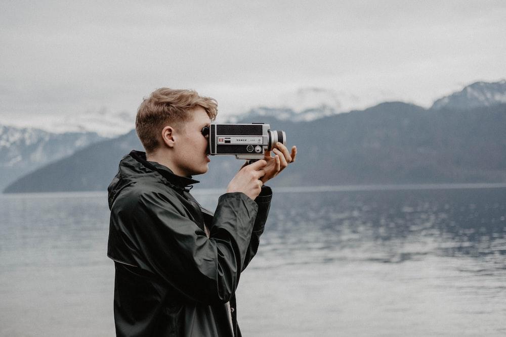 man taking video near body of water