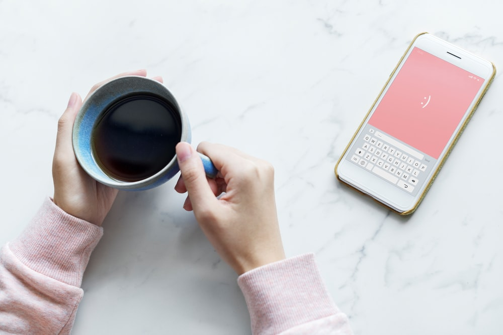 person holding cup of coffee near turned on white Android smartphone