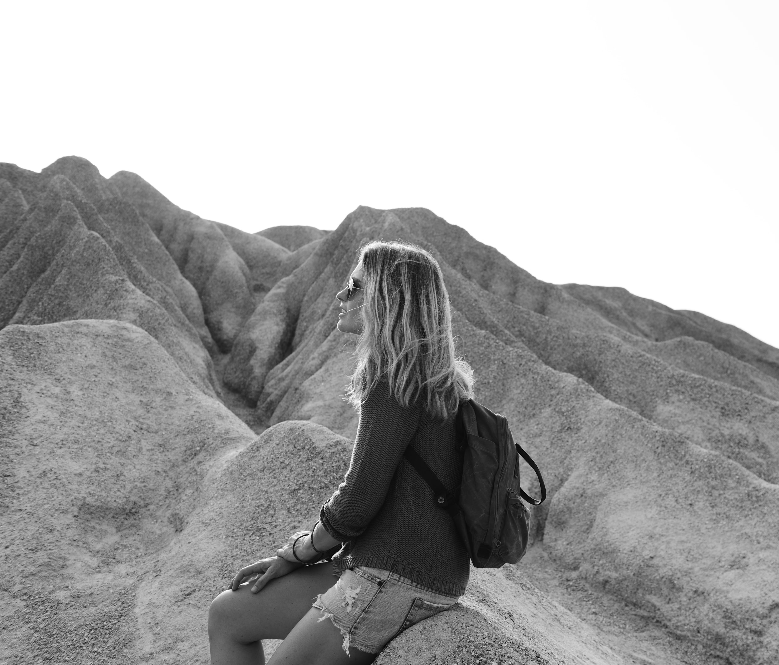 woman sitting on gray rock hill during daytime