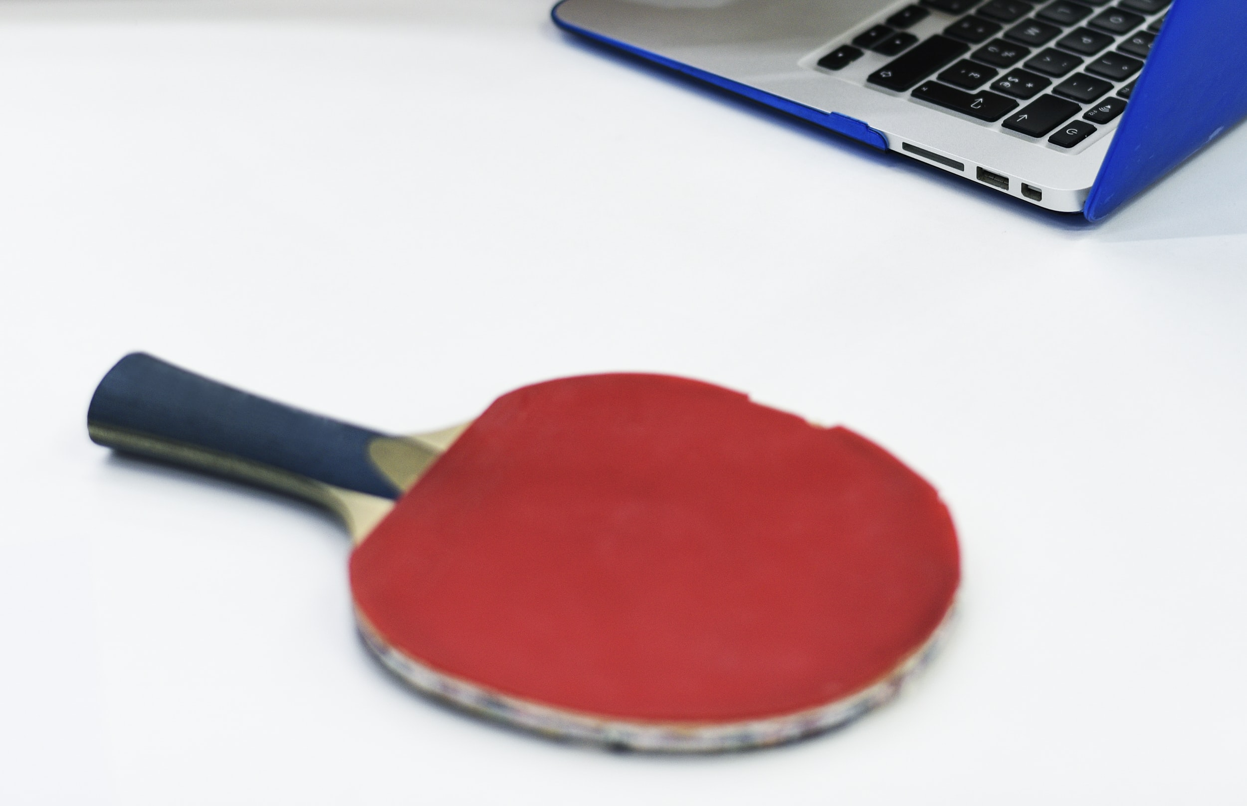 red and black pingpong racket beside of silver laptop computer