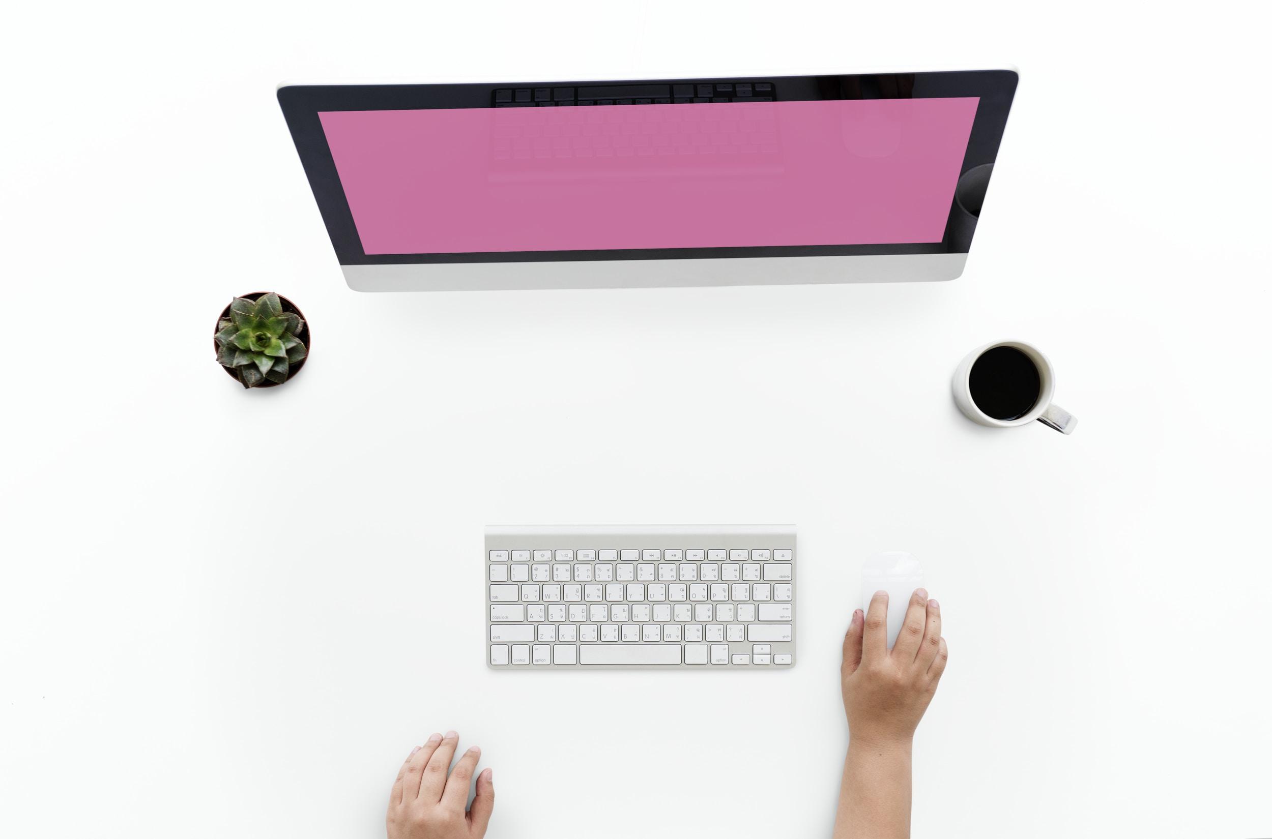 silver iMac and Wireless Keyboard on table with coffee mug