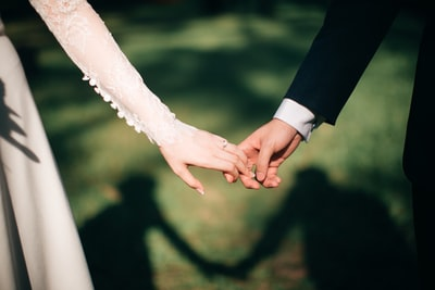 man and woman holding hands focus photo wedding teams background