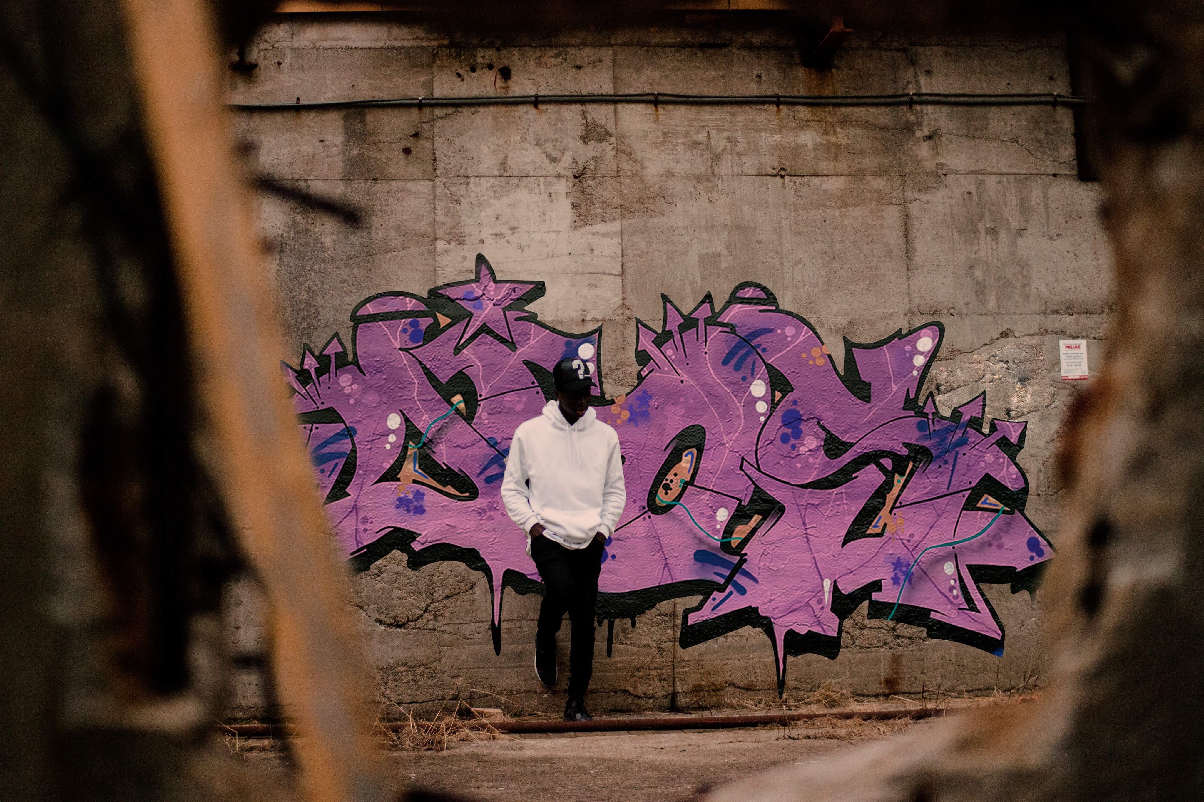 man in white pullover hoodie leaning on purple graffitied wall
