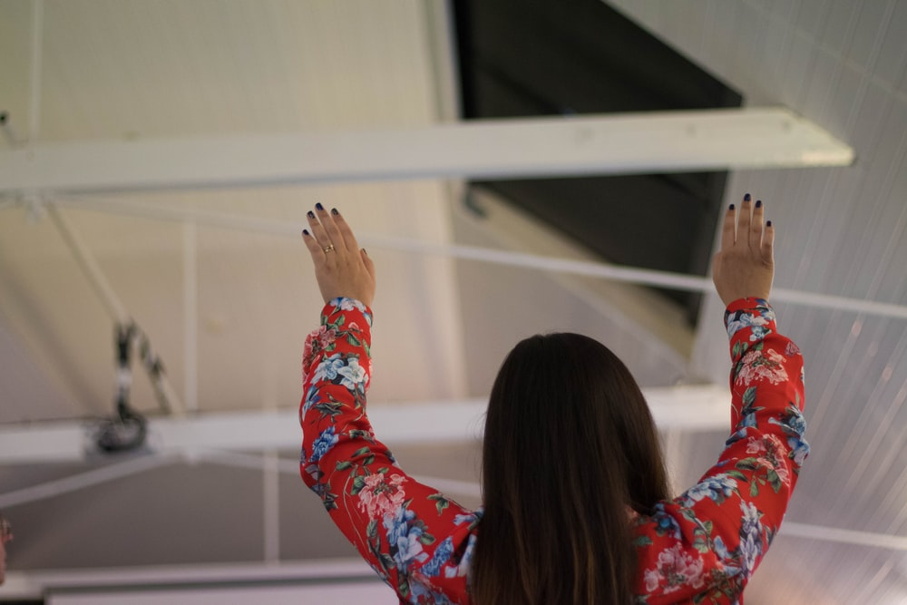 woman holding her hands up inside building structure