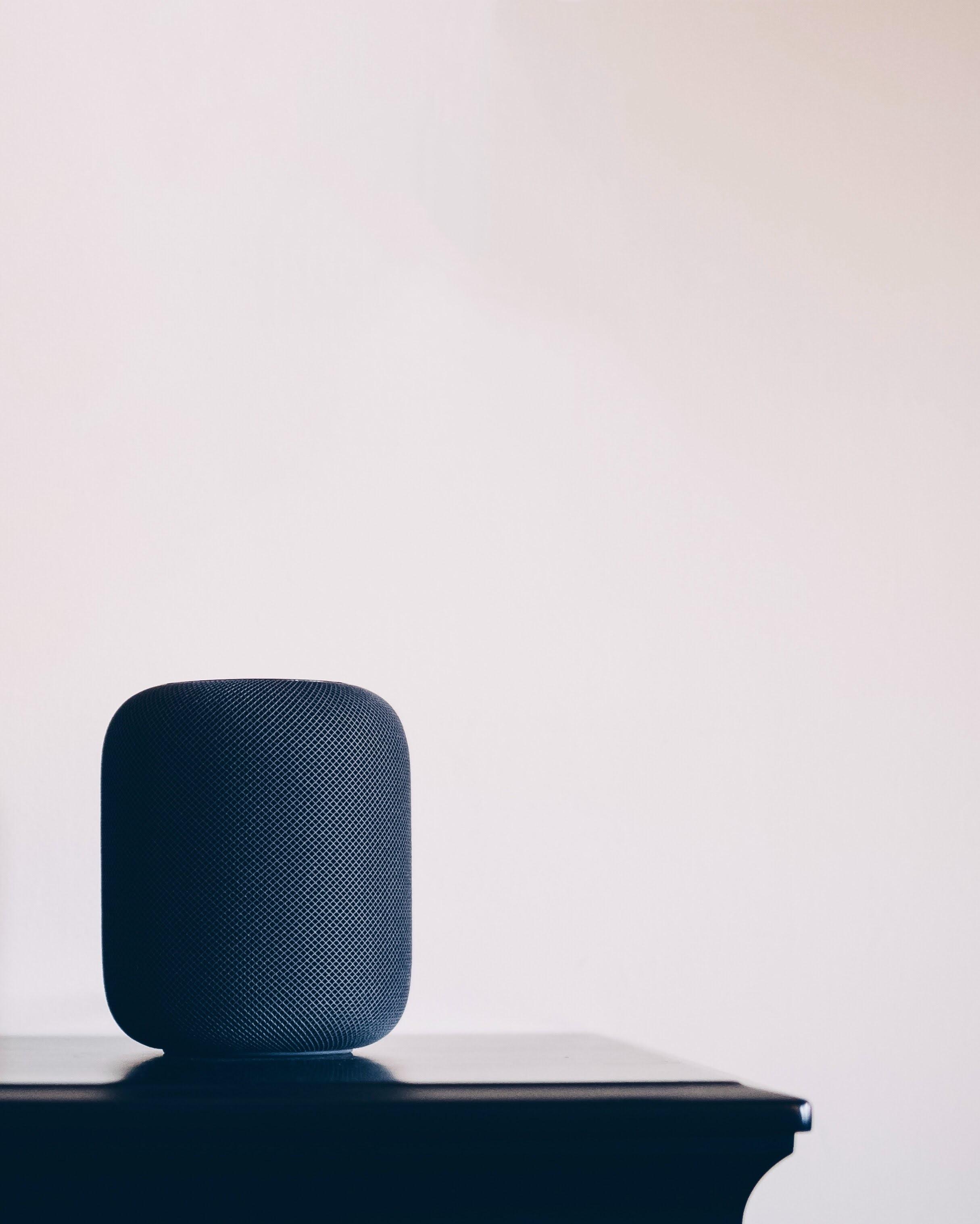 black Apple HomePod speaker on table