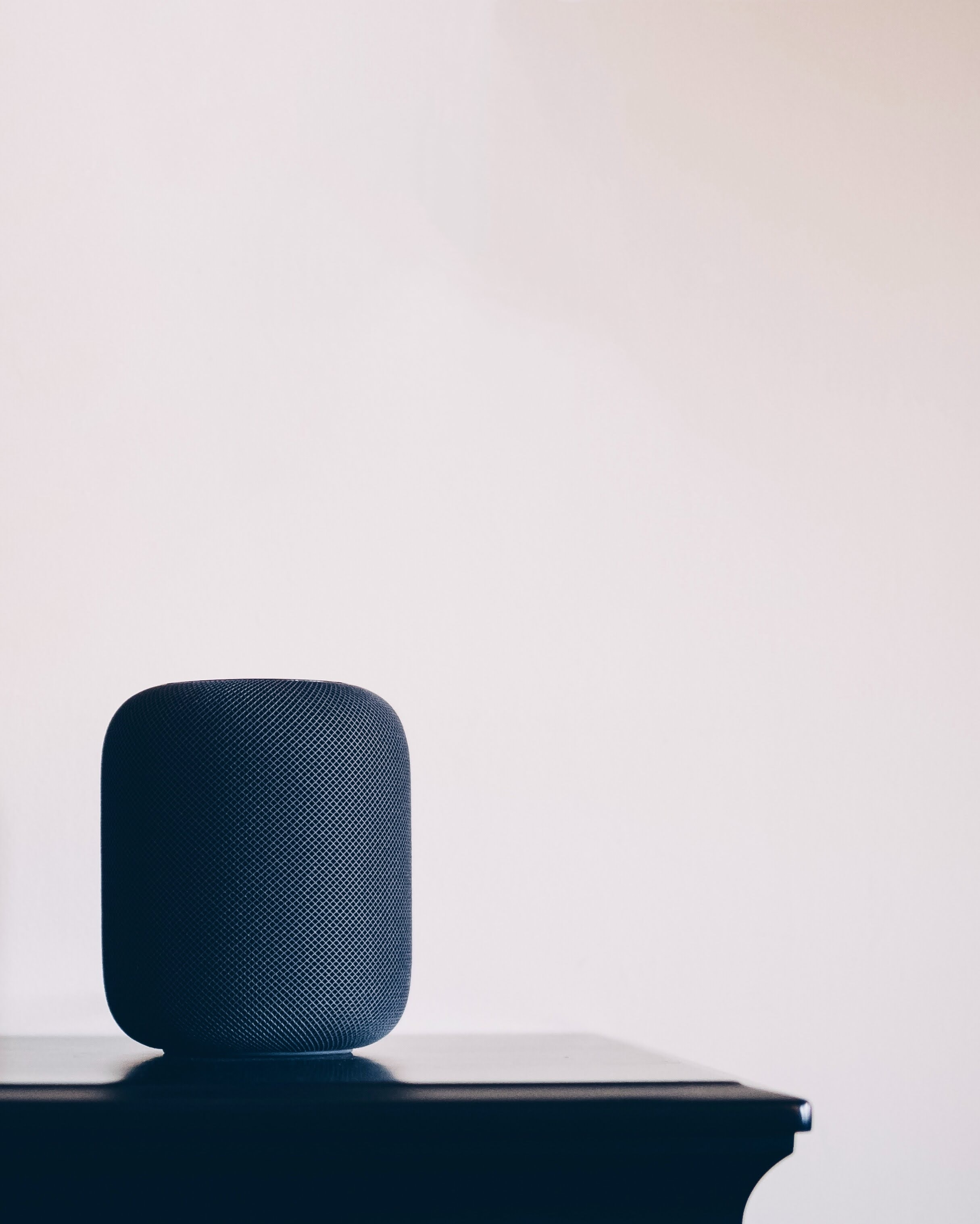 black Apple HomePod speaker on table