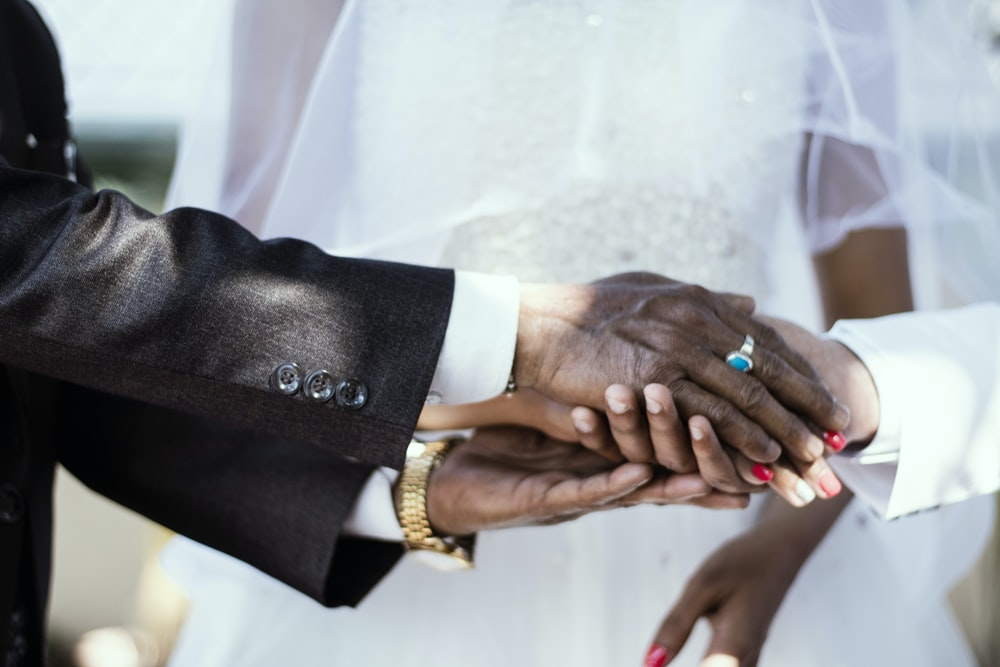 man holding hands white wearing silver-colored ring
