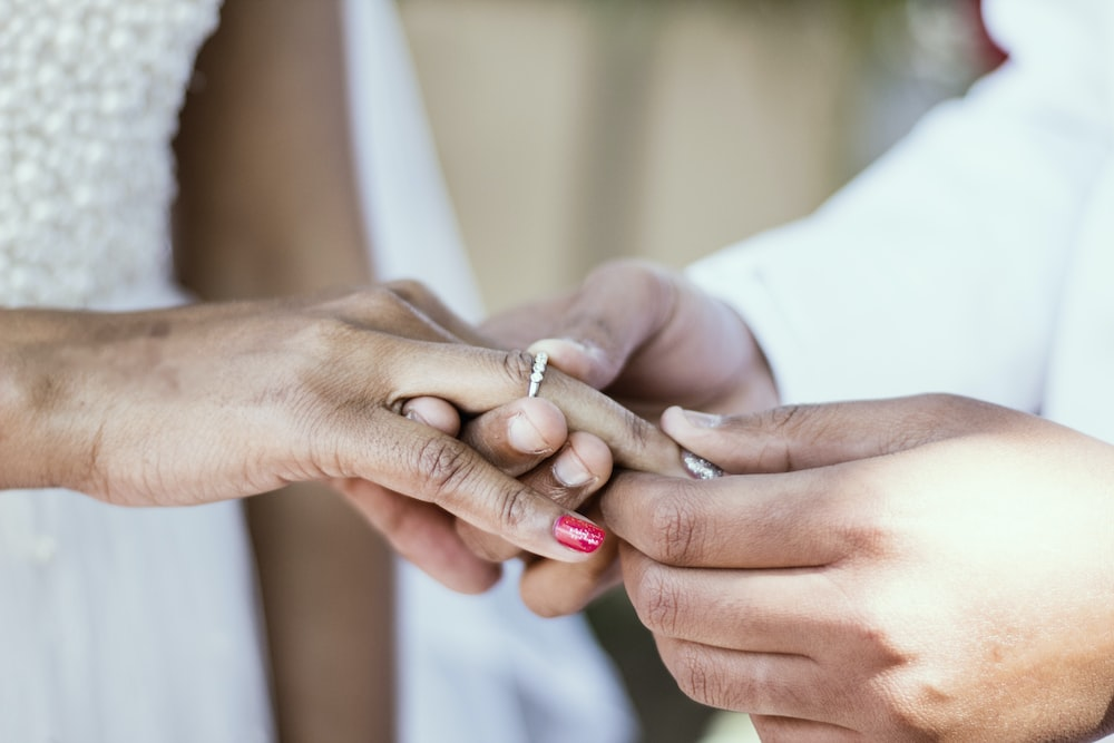 person putting ring on ring finger of woman