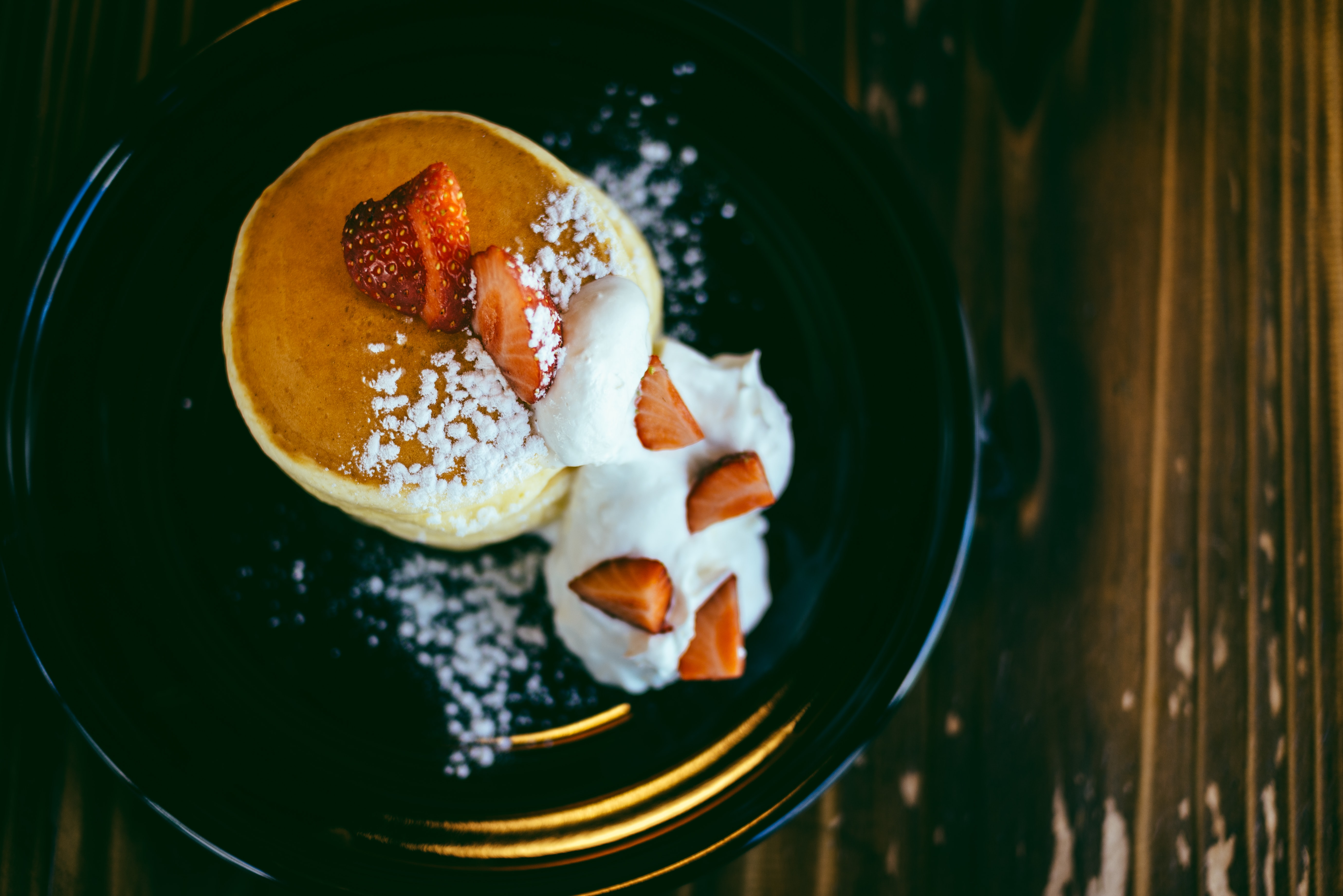 strawberry topped pancake with whip cream on round black ceramic plate