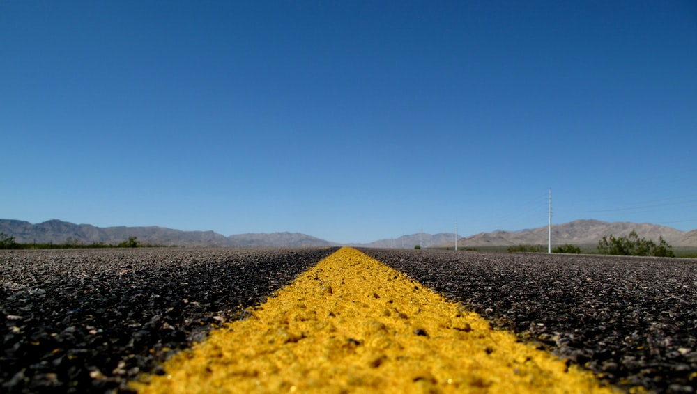 photo of black and yellow asphalt road under clear blue sky during daytime